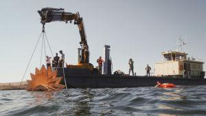 """Armi Nurmisen veistos """"Kalakoto"""" lasketaan veteen nosturilla Dalskär-saarella."""