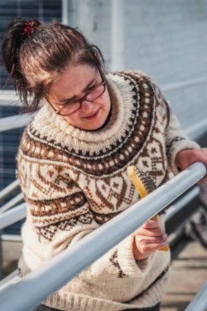 Villapaitaan pukeutunut nainen hankaa metallikaidetta metalliharjaksisella harjalla.