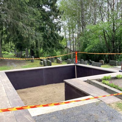 En stor, tom grav omgiven av rödgula varningsband. Graven har färdigställts intill ett monument över inbördeskriget i Heinola.