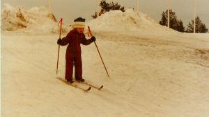 Gulnat foto av liten Tanja Poutianen som skidar i en brun halare.