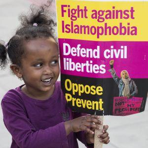 Flicka håller upp en skylt med texten: Kämpa mot islamofobi