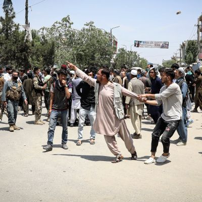 Väkijoukko reagoi järkyttyneesti sairaalahyökkäykseen. Yksi mies pitelee kiinni toisesta miehestä, joka on ryntäämässä jonnekin.
