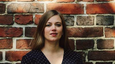 runoilija Anna Elina Isoaro seisoo tiiliseinän edessä