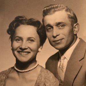 1950-luvun kuvassa nuori nainen helmikorvakoruissaan ja mies vaalea juhlapuku päällään.