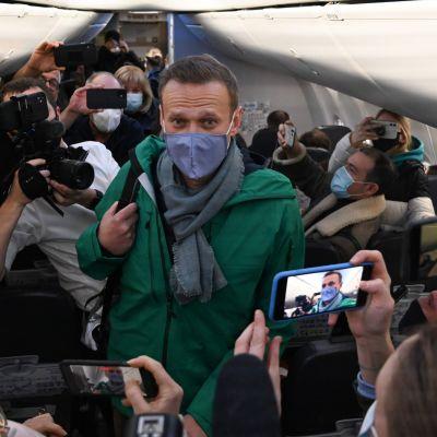 Aleksej Navalnyj ombord på ett flygplan 17 januari 2021. Han bär munskydd. Runt honom står massvis av människor som fotograferar honom.