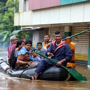 Människor tar sig fram i en gummibåt i Kerala i augusti 2018.