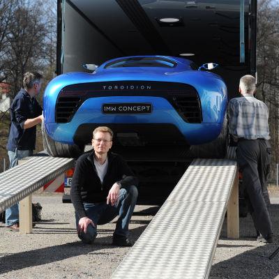 Pasi Pennanen poserar under sin superelbil Toroidion som rullas ut ur en transportbil.
