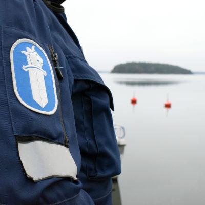 Polisens logotyp på ärmen av en polisrock. Havet och två röda bojar i bakgrunden.