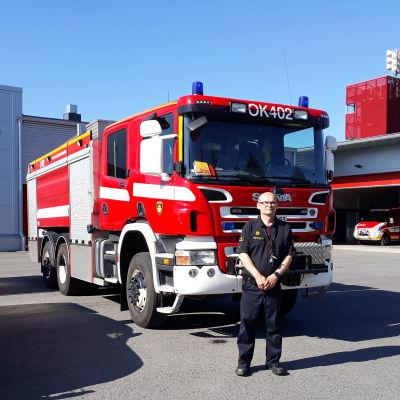 Ari Virtanen står vid en brandbil.