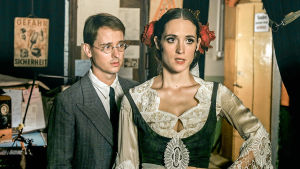 Mies ja nainen seisovat ehkä työhuoneessa tai ateljeessa, mies seisoo naisen takana ja katsoo häntä.