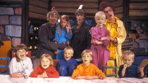 Kuvassa lapsia ja aikuisia rivissä. Katsovat kameraan ja laulavat. Miitta-tädin joulukalenteri.