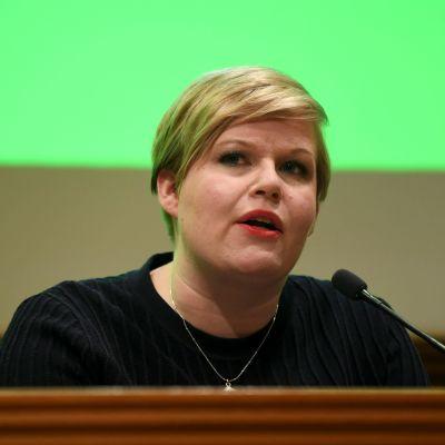Annika Saarikko framför en liten mikrofon.