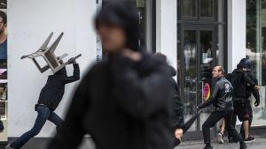 En demonstrant är på väg att kasta en stol mot en annan demonstrant i Chemnitz den 1 september 2018.