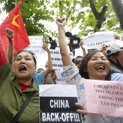 Vietnameser demonstrerar mot Kina med banderoller och slagord.