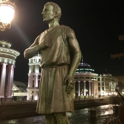En ny staty på en av broarna över floden Vardar i Makedoniens huvudstad Skopje föreställer en soldat från Alexander den stores armé som håller handen mot hjärtat på ett patriotiskt sätt
