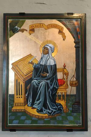 Målning av heliga Birgitta klädd i blått med gyllene gloria kring huvudet. Birgitta skriver i en bok och guds hand sänder strålar till den gyllene glorian.