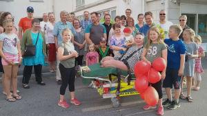 Iloinen ihmisjoukko sairaalan pihalla, keskellä raajoista amputoitu nainen perheineen.