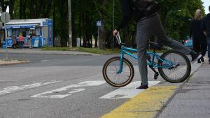 Cyklists fötter när de stigit av cykeln vid övergångsställe.