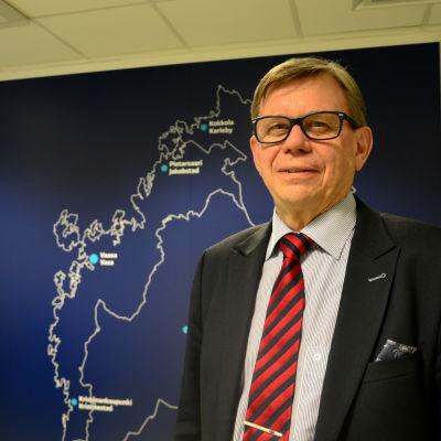 Olav Jern står i kostym framför en karta av Österbotten. På kartan är Kristinestad, Vasa, Jakobstad och Karleby utmärkt.