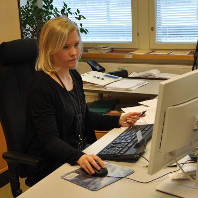 Äldre konstapel Sara Malm sitter vid sitt skrivbord i polishuset i Pargas.