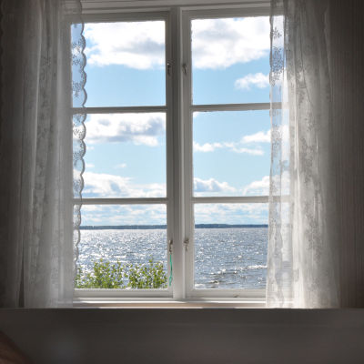 Havsutsikt från ett fönster. Vita tyllgardiner, sommar, glittrande hav.