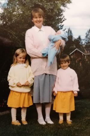 Ett gulnat fotografi av en kvinna. I famnen håller hon ett spädbarn och bredvid henne står två flickar i gula kjolar.