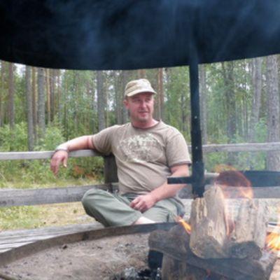 Matkailuyrittäjä Jarkko Peltola nuotion äärellä Ruunaalla.