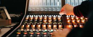 En hand ovanför ett mixerbord.