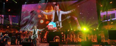 Långhårig man i lång vit kavaj med vit elgitarr runt axeln står på stor konsertscen. Storbildsskärm bakom med bild av samma man och text på ryska.