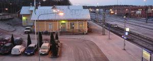 En gammal gul järnvägsstation, järnvägsspår, parkerade bilar med isiga vindrutor. Skymning.
