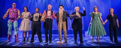 Många olika teaterkaraktärer står på en scen med blått ljus och sjunger.