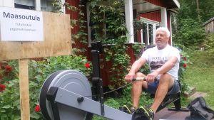 Pekka Ilmarinen demonstrerar roddmaskin som finns med på jubileumsjippot vid Porla i Lojo.