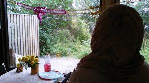 Asylsökande kvinna vid fönstret i sitt hem vid Raasepori Resort som ska stängas.