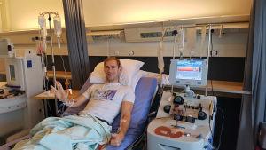 En man som ligger i en sjukhusbädd. Han har två slangar som är kopplade till vardera arm. Ur en arm åker blodet ut, in till en maskin bredvid, och genom andra armen kommer blodet in tillbaka. Runt honom finns också två droppställningar med dropp.