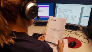 Kymsoten päivystysapupalvelun sairaanhoitaja työpisteellään kuulokemikrofoni päässään.