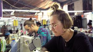 Mies ja nainen tehtaassa ompelukoneiden äärellä.