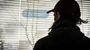 En man i 20-årsåldern står med ryggen mot kameran och tittar ut genom ett fönster med spjälgardiner. Stämningen är hotfull. Det är en dramatiserad bild som föreställer en nätbedragare.