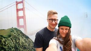 Nuori poika ja tyttö ison sillan edessä.