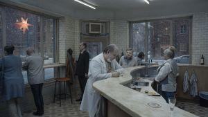 En tandläkare står vid en bardisk. Utanför fönstret snöar det.