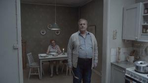 En man står i sitt kök och tittar rakt in i kameran. Hustrun sitter i bakgrunden vid bordet.