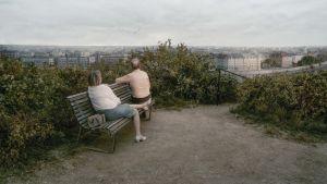 Ett par sitter på en bänk med ryggen mot kameran.