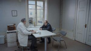 Psykiater och patient på varsin sida om ett bord.