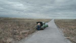 En man och en bil mitt i ett öde landskap.