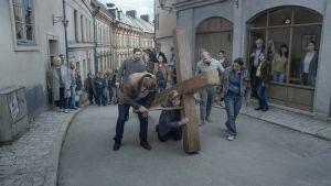 Bild på en man som släpar på ett kors i en scen ur filmen Om det oändliga.
