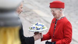 Drottning Margrethe II av Danmark iklädd röd dräkt tar emot en blombukett av president Sauli Niinistö utanför presidentens slott i Helsingfors.