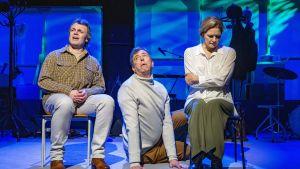 Två skådespelare sitter på stolar och emellan dem sitter en man på golvet och stirrar upp mot dem.