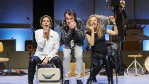 Tre skådespelare mejkar sig med ansiktena vända mot kameran.