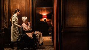 Maud skuffar fram en rökande Amanda som sitter i rullstol.