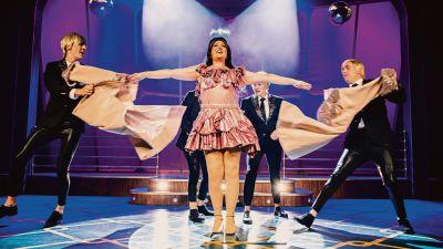 KAJ-medelmmarna i svarta kostymer dansar runt en sångerska i rosa klänning.
