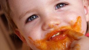 Pieni lapsi suun ympärys tomaattikastikkeessa